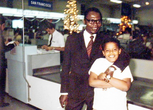 Image of Barack Obama Sr. and Jr. standing in front of a ticket counter purported to be located at the Honolulu International Airport.