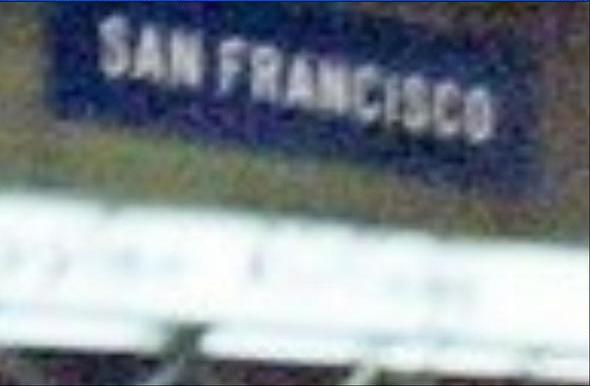 Close-up of the 'San Francisco' sign inside the airport terminal.